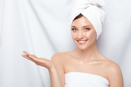 attractive young lady in bath towel on head pretending that she holding something on her arm, copy space, pretty girl keeps arm near shoulder