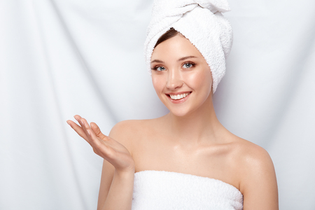 pretty girl with perfect smile in bath towel looking to the camera and holding her hand, copy space, spa and facecare treatment