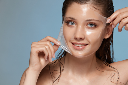 woman peels-off transparent facial mask and smiling to the camera on blue, happy anf fresh girl with perfect skin