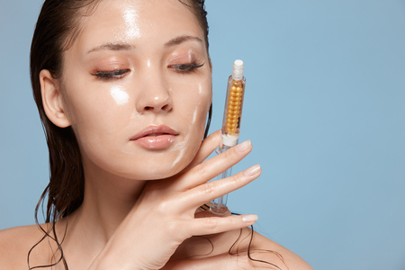 beautiful woman with wet face holding cosmetology injection, copy space, close-up of pure natural face with syringe