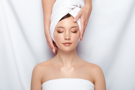 attractive woman lying down on spa theraphy in bath towel, customer of spa receiving facial treatment with beautician