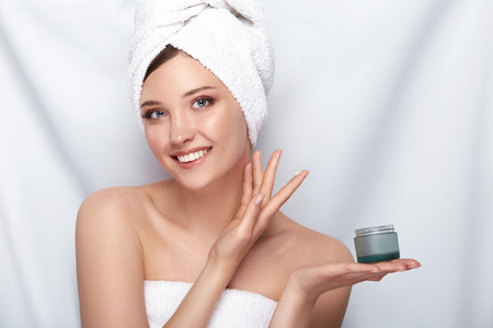 beautiful girl in bath towel on her head holding cream and touching her face on white,facial treatment with perfect skin lady Standard-Bild
