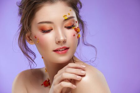 beautiful woman with orange make-up touching her shoulder isolated on purple background, elegant spring face look with natural flowers 写真素材