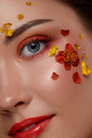 beautiful woman face looking to the camera with colorful make-up and flowers on it, gorgeous flowered orange mua Standard-Bild