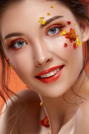 close-up portrait of pretty girl with orange make up and flowers on her face looking to the camera, fashion beauty Standard-Bild
