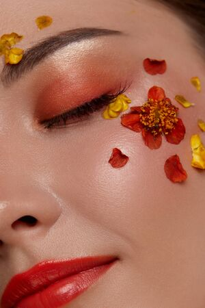 happy and beautiful woman close-up with fashionable orange make-up and red flowers, elegant colorful mua