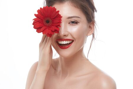 beautiful brunette with red lips and big flowers closing her one eye smiling to the camera, luxury model face with floral concept 写真素材 - 127313517