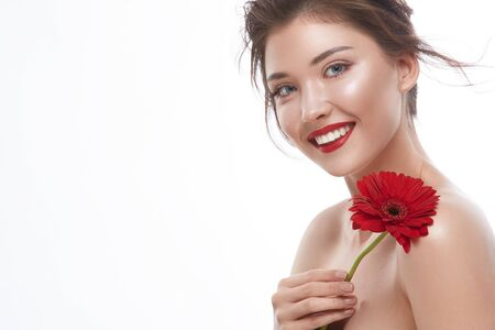 pretty woman with perfect smile holding red flower and looking to the camera, copy space, beautiful girl with red lipstick smiling