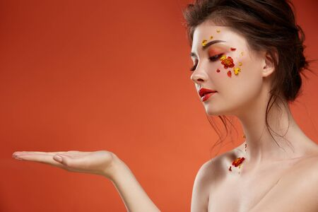 pretty woman with orange make up holding her arm isolated on orange, copy space, natural and beauty spring concept 写真素材