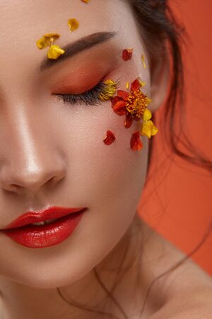 close-up of half woman face with beautiful flowers and orange make up, pretty eyes mua , colorful beauty concept 写真素材 - 127313554