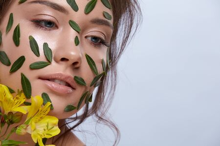 attractive female with perfect skin and leaves on her face having flowers, copy space, close-up, green concept