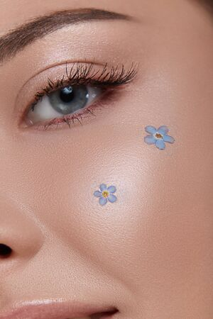 woman eye with perfect nude make-up and forget-me-nots on the cheek, close-up of girl face wih blue flowers