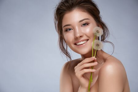 pretty woman with natural make-up and naked shoulders holding dandelions and smiling, copy space, happy and beautiful natural care