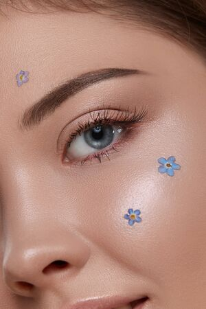 romantic woman's eye looking to the camera with fresh blue flowers on cheek, close-up of woman face with forget-me-nots and shiny mua