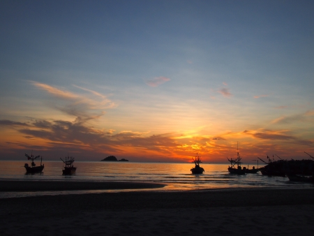 Silhouette seashore with fishing boats photo
