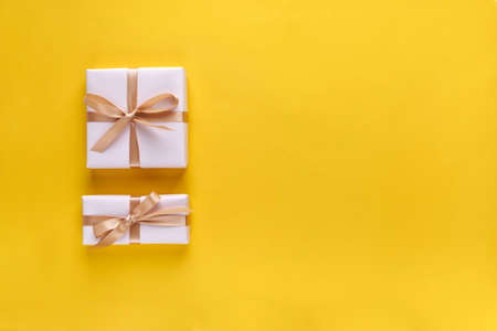 Gift box with ribbon and bow on color background and space for text. Top view