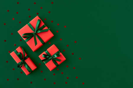 Red gift boxes with stars confetti on green background. Christmas card. Flat lay. Top view with space for text Foto de archivo
