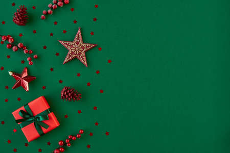Christmas, New year composition. Gift box and holiday decorations on green background. Flat lay. Top view with copy space 免版税图像