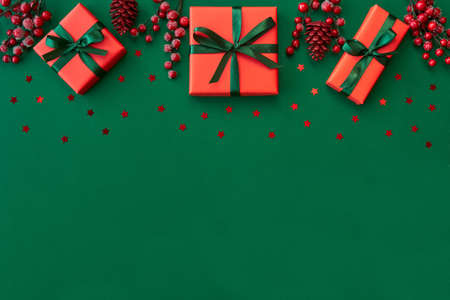Christmas, New year composition. Gift boxes, holiday decorations on green background. Flat lay. Top view with copy space