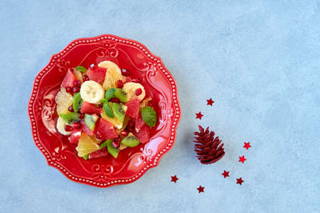 Winter fruit salad in red plate on stone background with holiday decoration. Top view with copy space