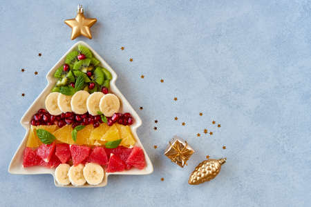 Christmas background with fruit salad in fir tree shaped plate and holiday decoration. Top view flat lay