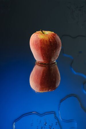 apple with reflection on blue background