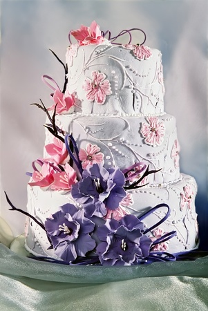 cake decorating: Bellamente decorado pastel de boda con flores de color p�rpura y rosa