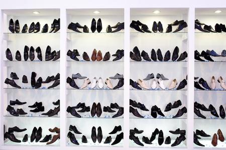 comprando zapatos: Hombres zapatos en estantes de vidrio Foto de archivo