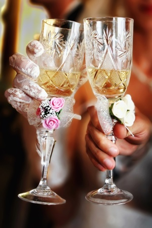 Glass of champagne in a hand of the groom and bride