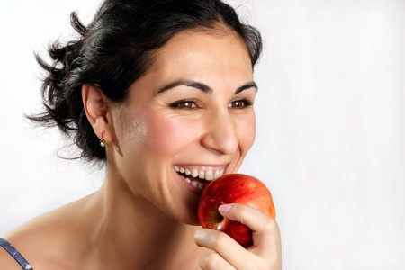 Smiling woman eating red apple