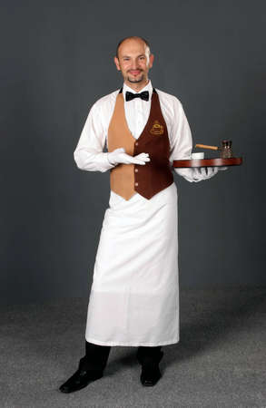 Waiter in uniform with percolator and cup of coffe.  Stock Photo