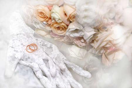 Close-up de guantes, anillos y flores románticas Foto de archivo