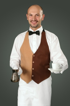 percolator: Waiter in uniform with percolator and cup of coffe.  Stock Photo