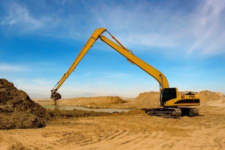transporte terrestre: Excavadora de naranja en el canal de riego en el desierto de la Construcción