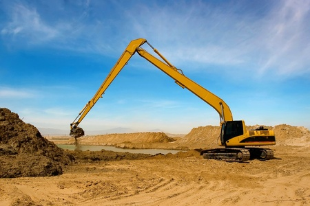 industrial objects equipment: Orange excavator  at Construction irrigation canal in Desert