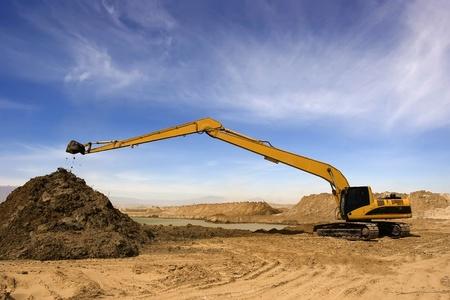 砂漠に建設潅漑運河でオレンジ色の掘削機
