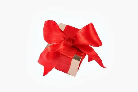 A gold box tied with a red satin ribbon bow  A gift for Christmas, Birthday, Wedding, or Valentine photo