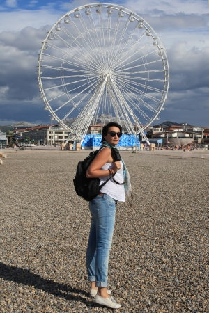 knapsack: Young woman traveling with a backpack on the coast of the Mediterranean sea  Ferris wheel is on a background