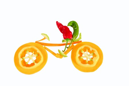 Healthy eating. Two little funny peppers on bicycle. photo