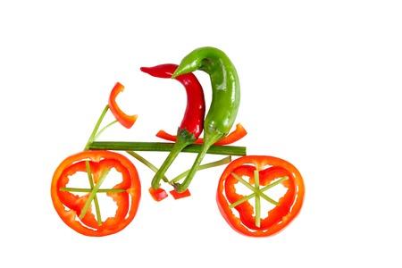 Gesunde Ernährung Zwei kleine lustige Paprika auf dem Fahrrad