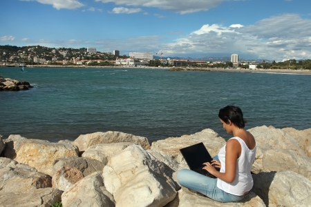 Young woman sitting on the beach and working at a laptop photo