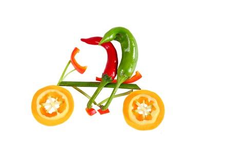 Gesunde Ernährung. Zwei kleine lustige Paprika auf dem Fahrrad.