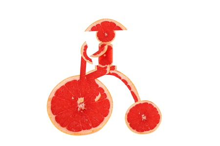 Healthy eating  Funny vintage bike  made of the grapefruit  slices with  little man photo