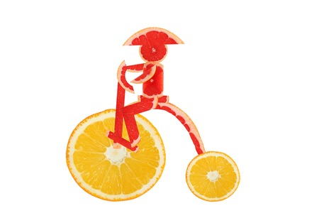 Healthy eating. Funny vintage bike  made of the orange  slices with  little man photo