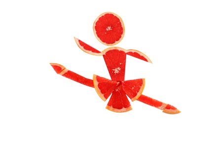 Healthy eating. Funny little danser made of the grapefruit slices. Stock Photo