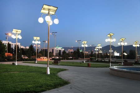 Alley in the park with a solar-powered lanterns. Night view.