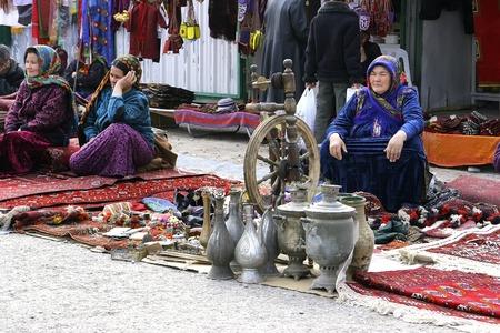 Ashgabat, Turkmenistan - February 26.  Three unidentified  Asian women on oriental bazaar. Asian women sell traditional utensil.  Ashgabat, Turkmenistan -  February  26. 2013.