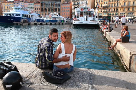 MARSEILLE - JULY 2, 2014: Old port (Vieux-Port) with young people sitting on the quay on July 2, 2014, Marseille. Marseille is Frances largest city on the Mediterranean coast and largest commercial port.