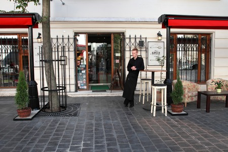 buda: BUDAPEST - JUNE 27:  The waiter stands at the entrance to the restaurant in historic district of Budapest - Buda. Buda - part of the city, situated on the high banks of the Danube. On June 27, 2014 in Budapest Hungary.