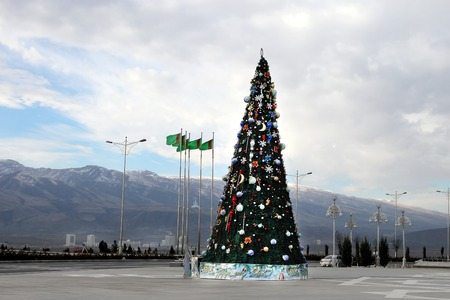 Christmas fir-tree on a square of Ashgabad and mountains as background photo